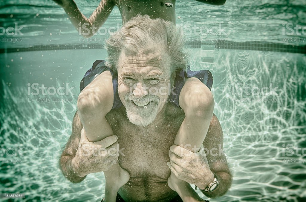 Grandpa plays with his grandson underwater in a pool in summer stock photo