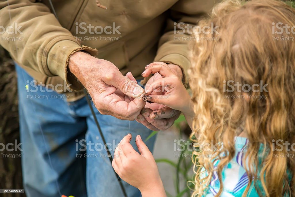Grandpa Teaching Granddaughter How To Bait Fish Hook stock photo