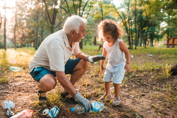 Grandpa teaching his granddaughter to keep the environment clean stock photo