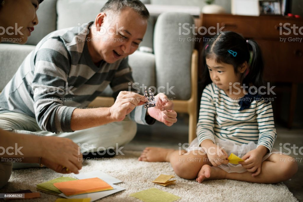 Grandparent palying with niece at home stock photo