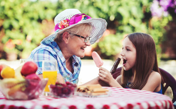 Grandparenting. Cute little girl eating ice cream with her grandmother. Lifestyle, family life stock photo