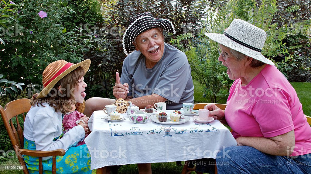 Grandparents and beautiful grandaughter having fun at a tea party stock photo