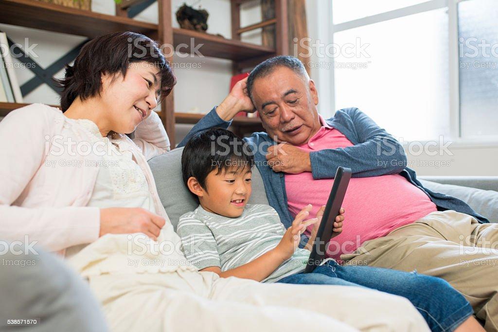 grandparents and grandchild sat on sofa using digital tablet stock