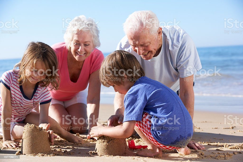 Grandparents And Grandchildren Building Sandcastle On Beach royalty-free stock photo
