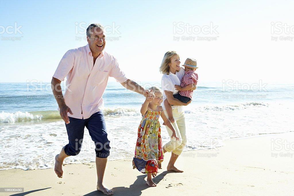 Grandparents And Grandchildren Enjoying Beach Holiday stock photo
