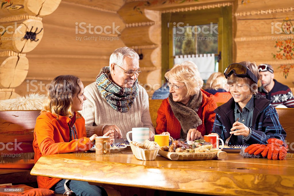 Grandparents and grandchildren having lunch after skiing Grandparents and grandchildren wearing winter clothes sitting in a mountain restaurant after skiing, talking and enjoying dinner. 60-64 Years Stock Photo