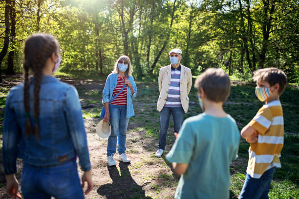 Grandparents and grandchildren meeting in park during COVID-19 pandemic stock photo