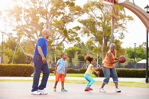 Grandparents And Grandchildren Playing Basketball Together stock photo