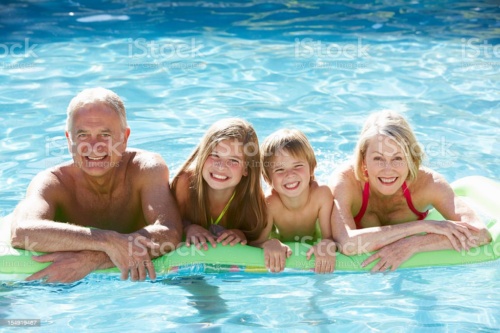 Grandparents And Grandchildren Relaxing In Swimming Pool Together royalty-free stock photo