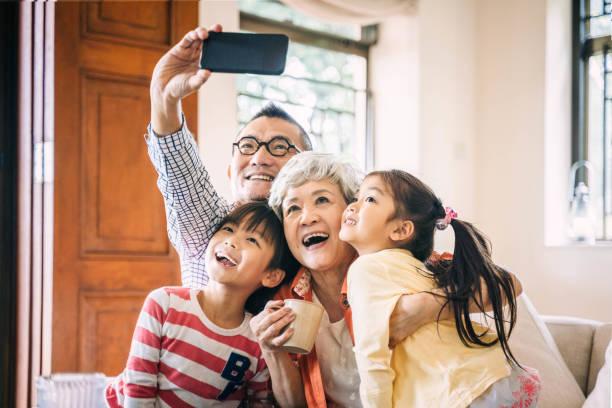 Großeltern und Enkelkinder sitzen auf Sofa nehmen Selfie – Foto