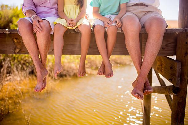 großeltern und enkelkinder sitzen zusammen an einem anlegesteg - granny legs stock-fotos und bilder