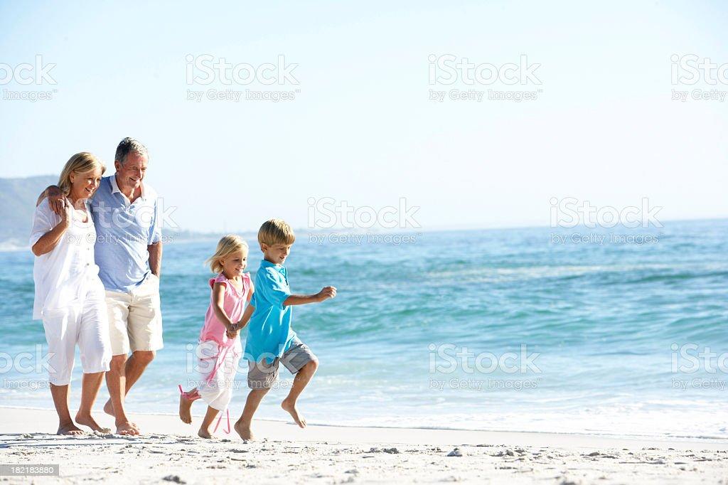Abuelos y nietos caminando por la playa - foto de stock