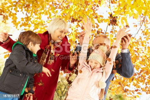 Grandparents And Grandchildren With Leaves In Autumn Garden Smiling Laughing Playing Embracing Family-Time Outdoor Caption