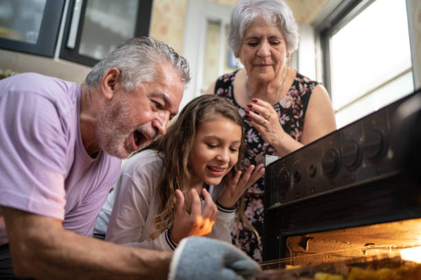 Grandparents and Granddaughter Checking the Traditional Turkey for Christmas Dinner stock photo