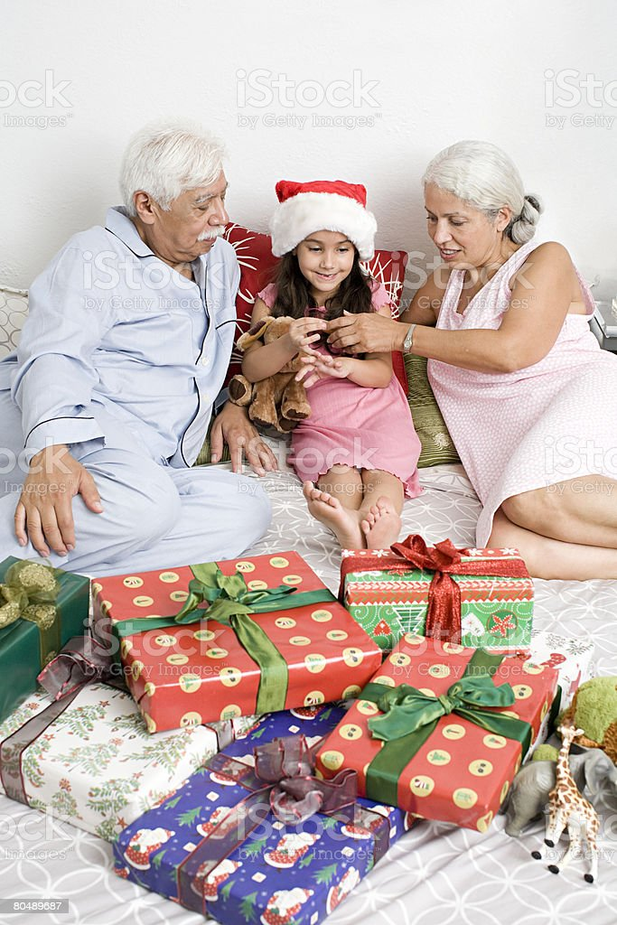 A grandparents and granddaughter in bed with gifts royalty-free stock photo