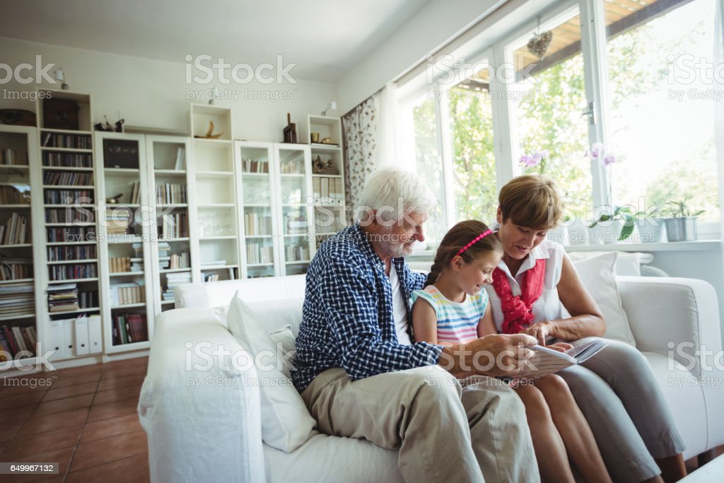 Grandparents and granddaughter looking at photo album in living room stock photo