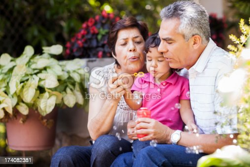 istock Grandparents and granddaughter making bubbles 174082381