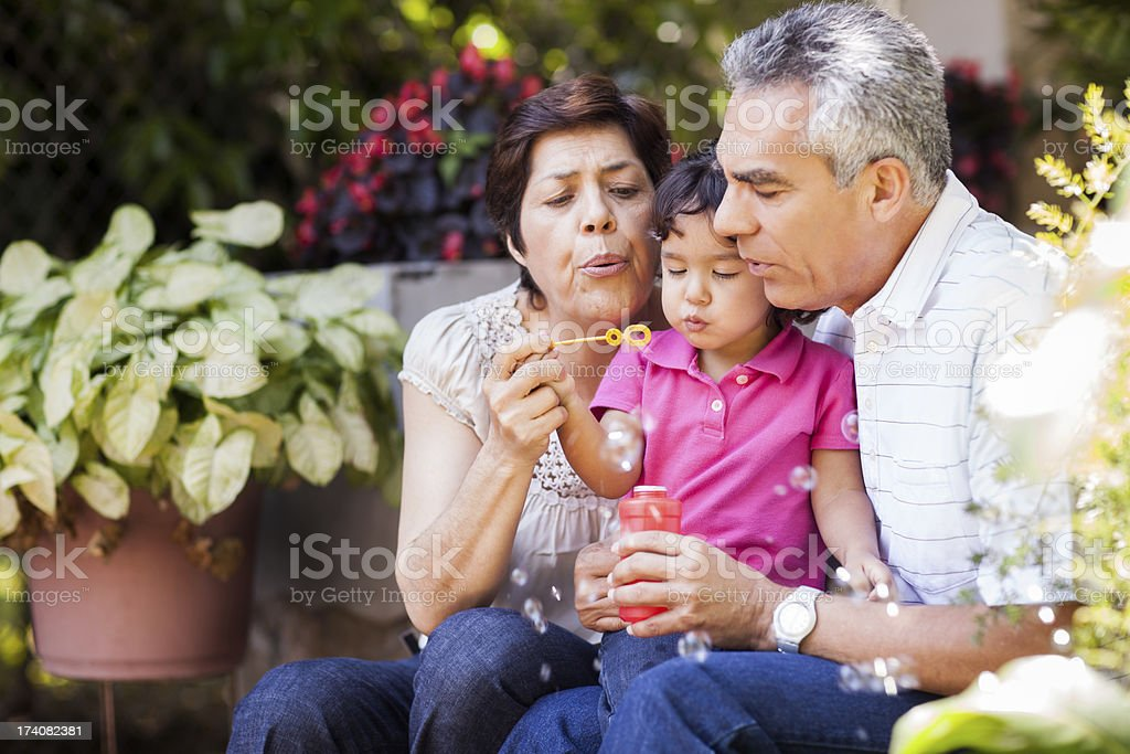 Grandparents and granddaughter making bubbles stock photo