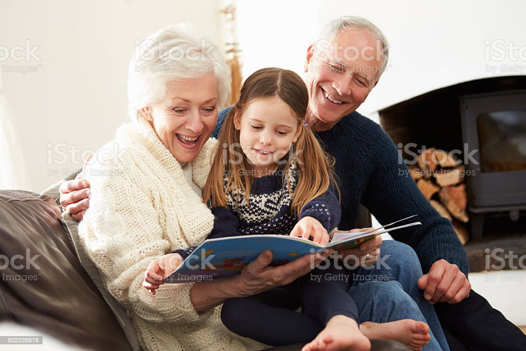 Grandparents And Granddaughter Reading Book At Home Together stock photo