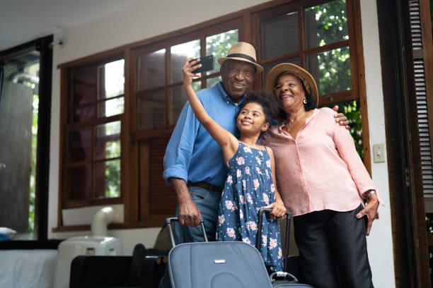 großeltern und enkeltochter unter selfies nach der ankunft in einem hotel - afrika urlaub stock-fotos und bilder
