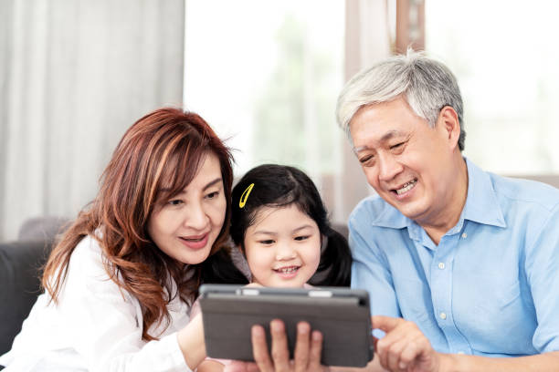 Grandparents and Granddaughter using technology digital tablet on sofa in living room. Happy asian Grandpa and Grandma using internet by tablet pc with little girls. stock photo