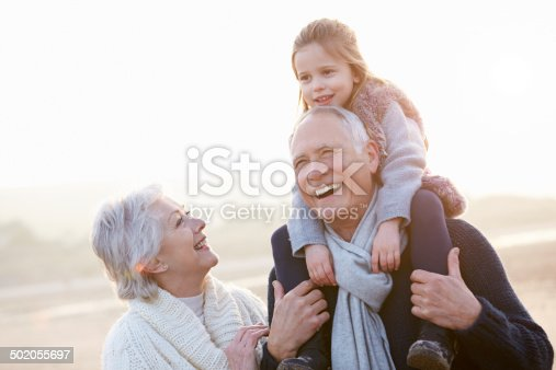 istock Grandparents And Granddaughter Walking On Winter Beach 502055697