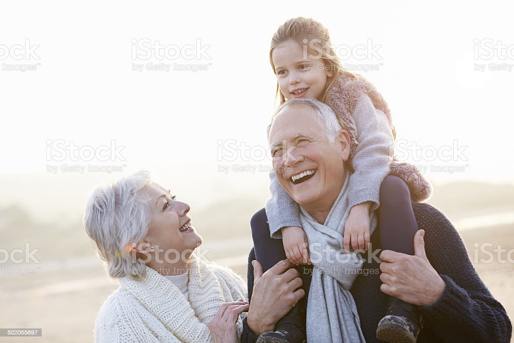 Grandparents And Granddaughter Walking On Winter Beach stock photo