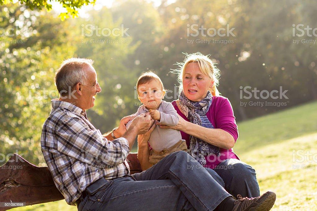 Abuelos y nieto en el parque - foto de stock