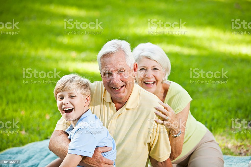 Grandparents and grandson laughing together outdoors stock photo