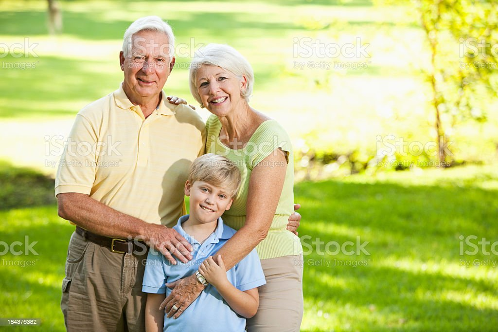 Grandparents and grandson standing outdoors stock photo