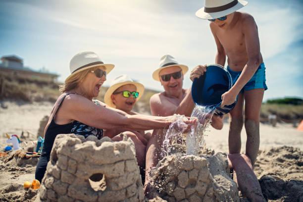 grands-parents et petits-fils jouant ensemble dans le sable sur la plage - chateau de sable photos et images de collection