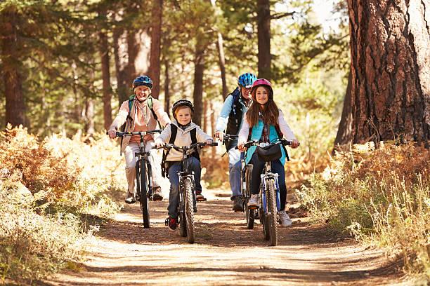 Nonni e bambini in bicicletta sulla foresta sentiero, California - foto stock