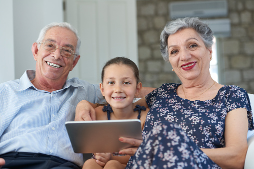 Grandparents and little girl with digital tablet