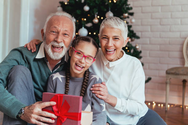 Grandparents and their granddaughter gathered around a Christmas tree, smiling stock photo