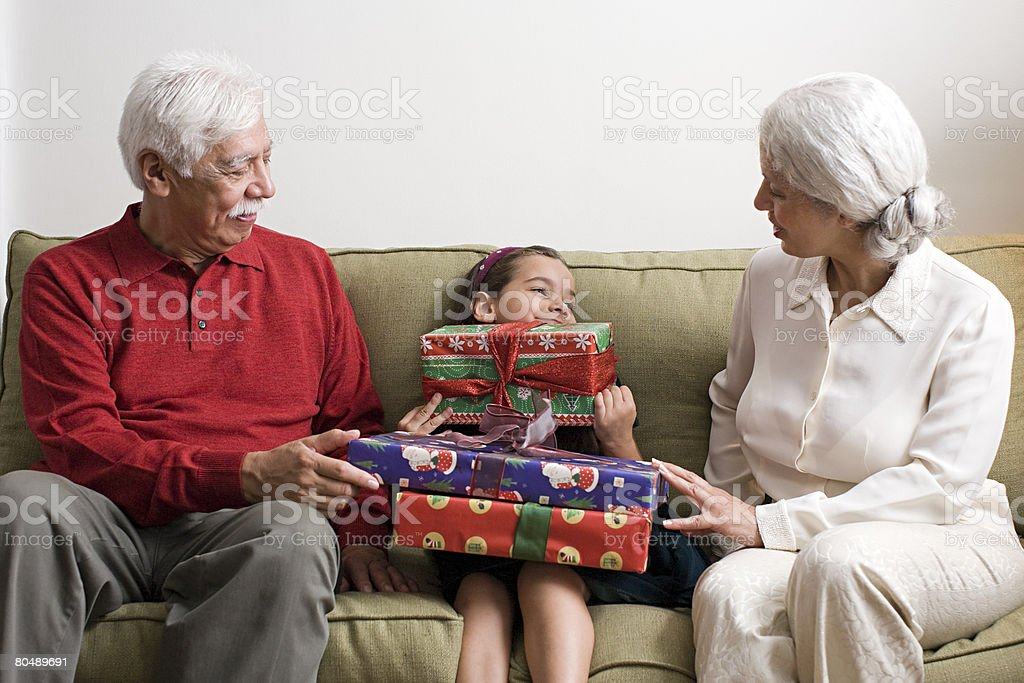 Grandparents and their granddaughter with gifts royalty-free stock photo