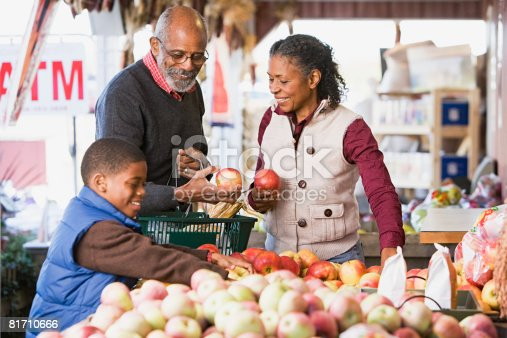 istock Grandparents and their grandson choosing apples 81710666