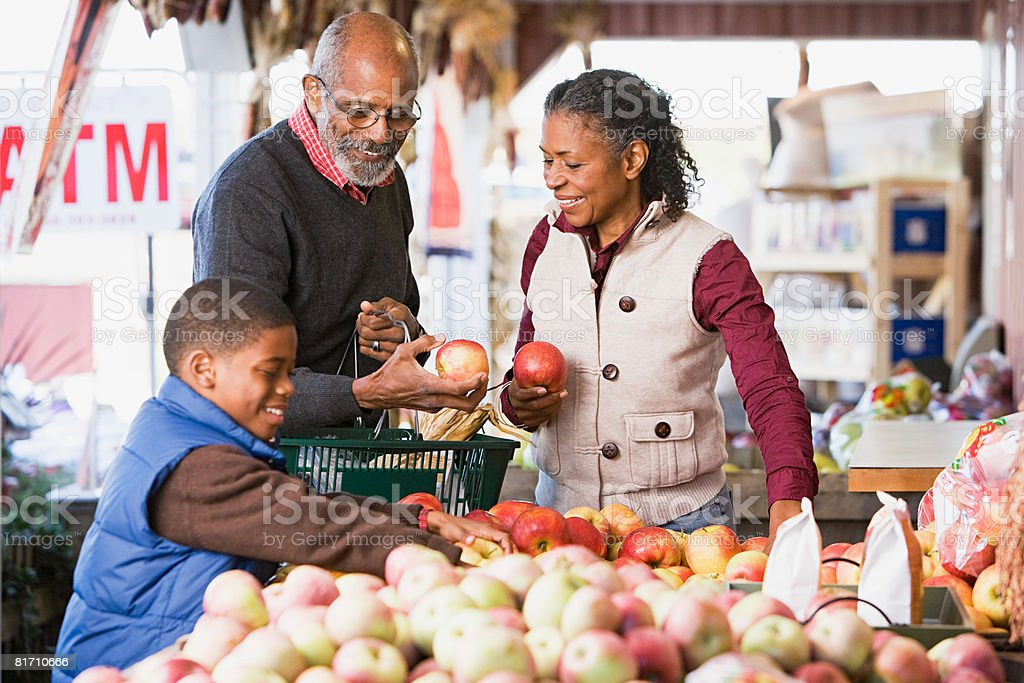 Grandparents and their grandson choosing apples stock photo
