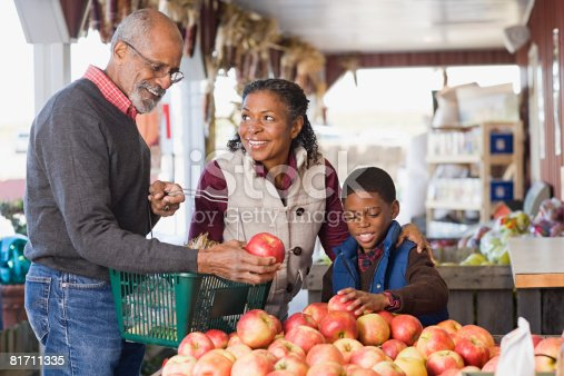 istock Grandparents and their grandson choosing apples 81711335