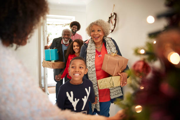 grandparents being greeted by family as they arrive for visit on christmas day with gifts - family christmas imagens e fotografias de stock