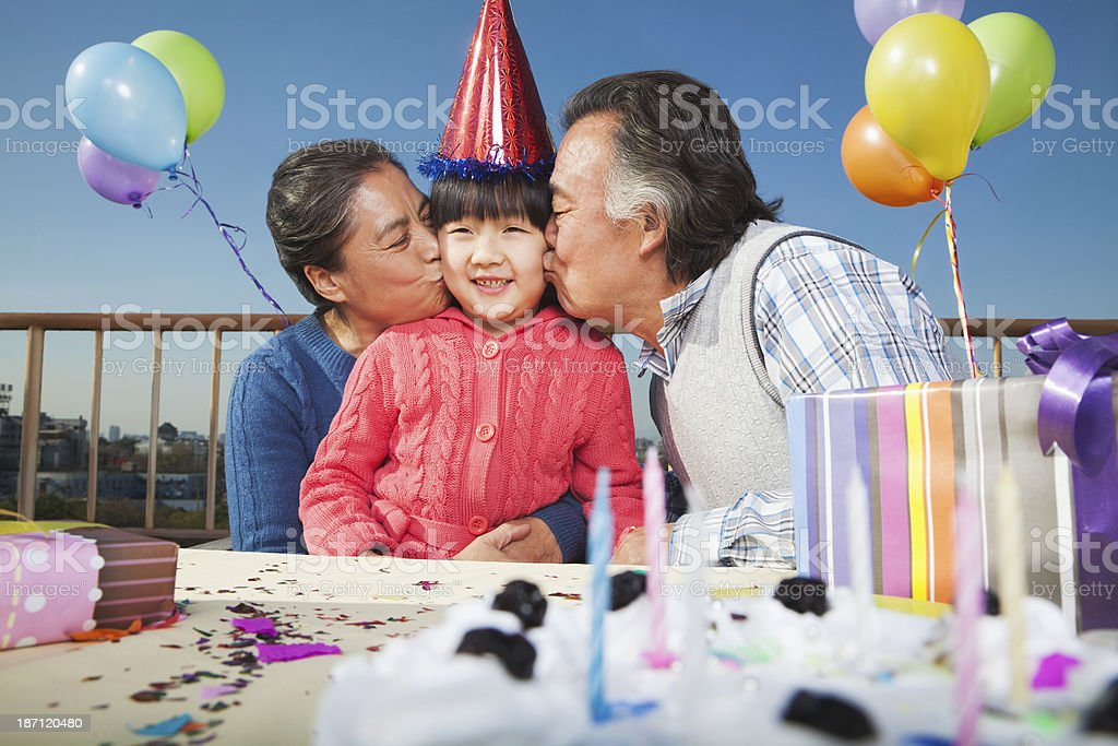 Grandparents celebrating birthday of granddaughter royalty-free stock photo