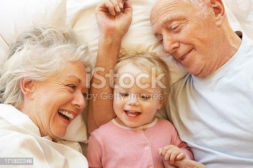 istock Grandparents Cuddling Granddaughter In Bed 171322246