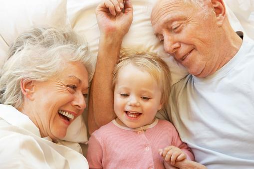 Großeltern Kuscheln Enkelin Im Bett Stockfoto und mehr Bilder von 12-17 Monate