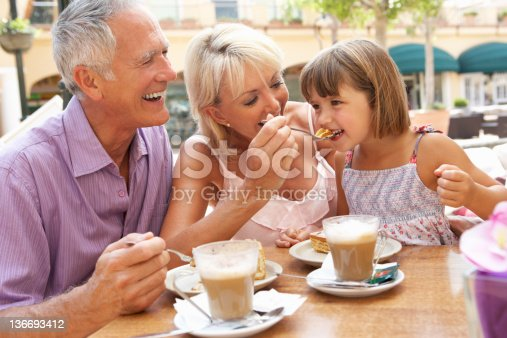 Grandparents With Granddaughter Enjoying Coffee And Cake In Caf
