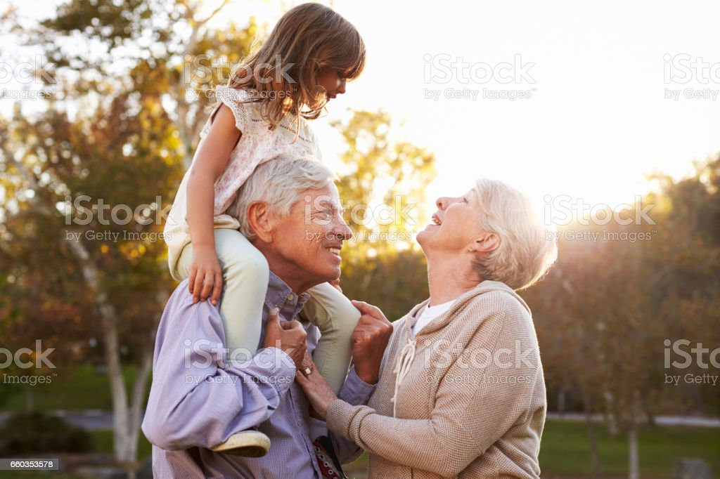 Grandparents Giving Granddaughter A Shoulder Ride In Park – zdjęcie