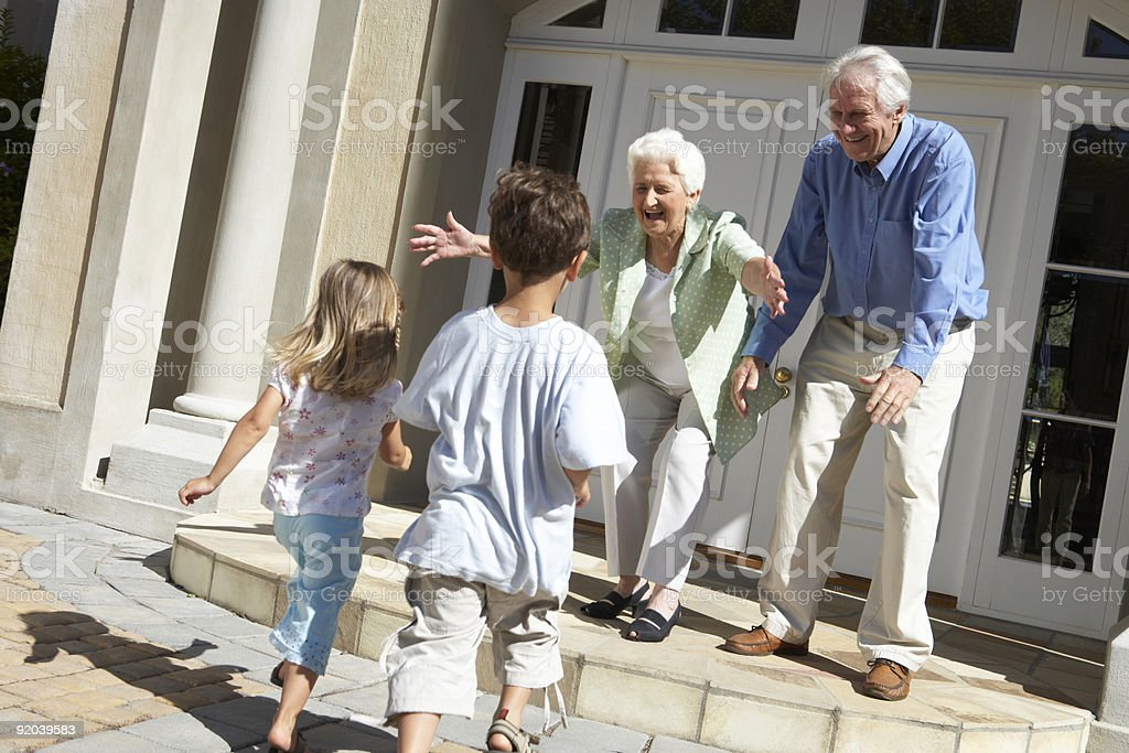 Grandparents greeting grandchildren on the steps of a house stock photo