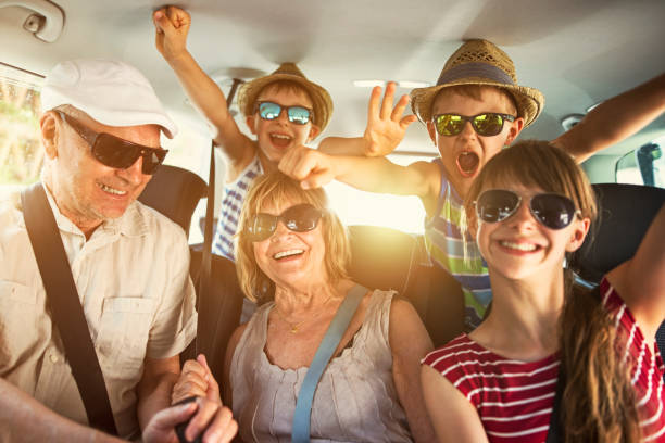 grandparents having fun on road trip with grandchildren - car interior stock photos and pictures