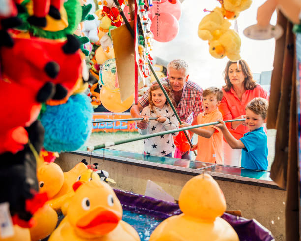 grandparents help their grandchildren hook a duck - carnival stock photos and pictures
