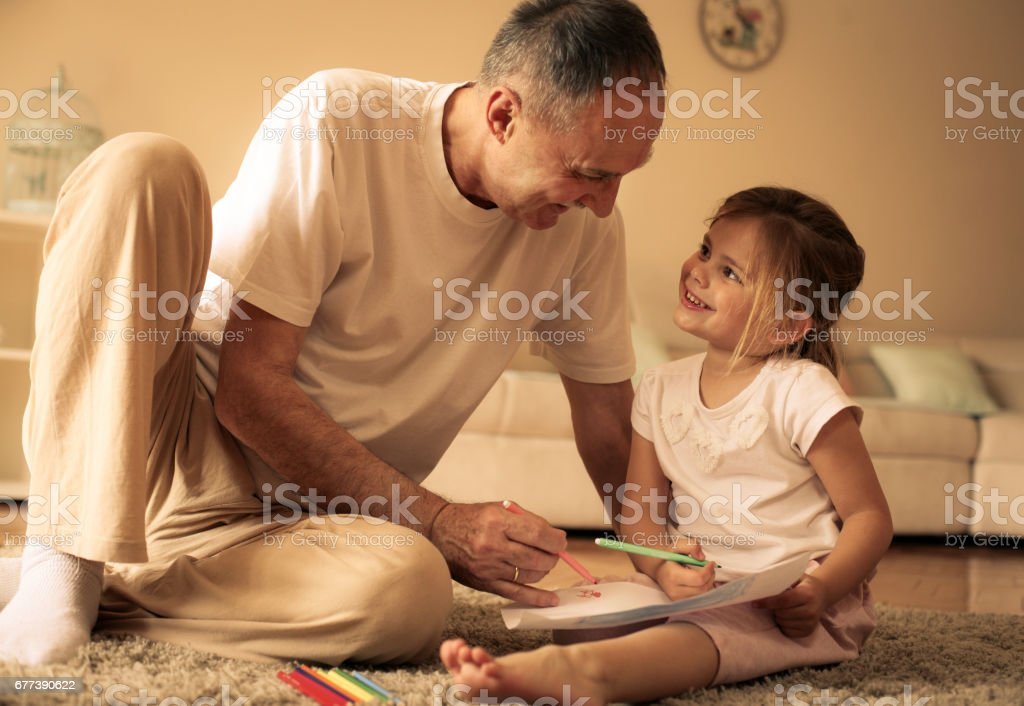 Grandparents help their granddaughter to write home. stock photo