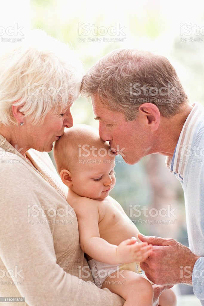 Grandparents holding and kissing baby royalty-free stock photo