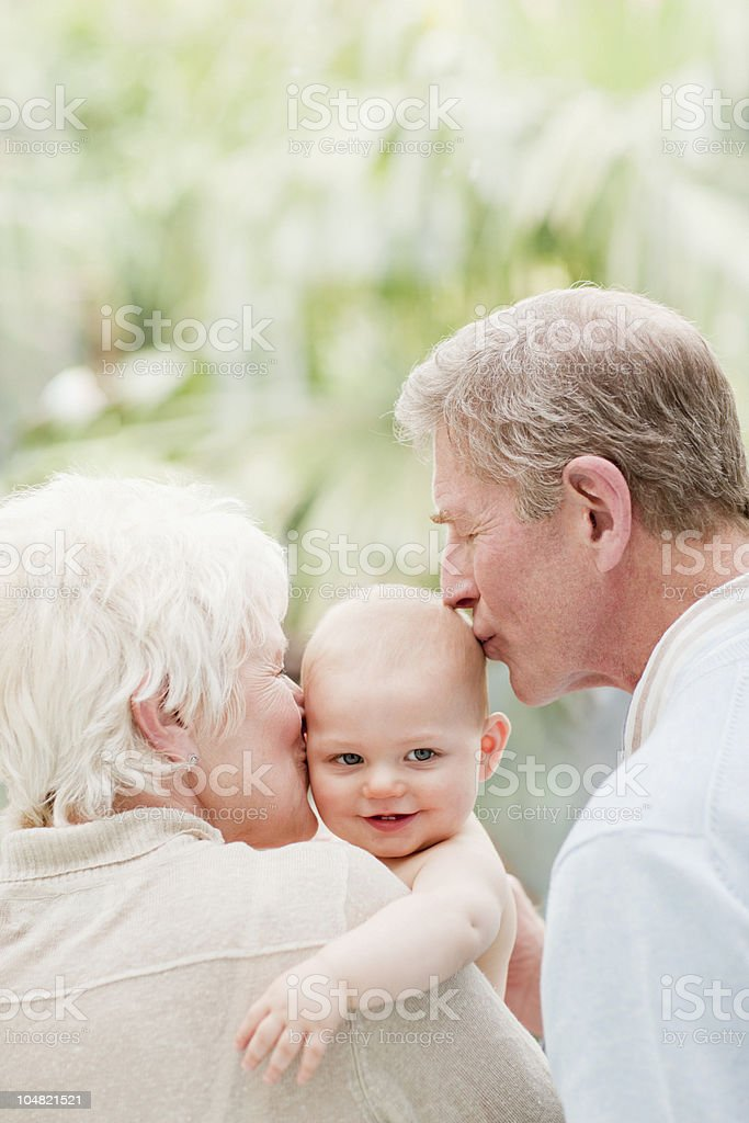 Grandparents holding and kissing smiling baby royalty-free stock photo